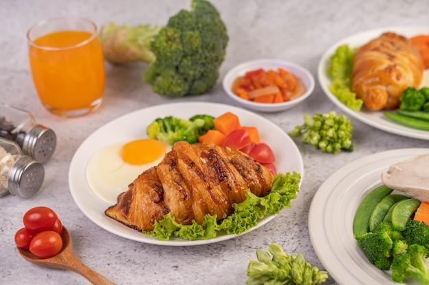 Завтрак, состоящий из хлеба, яичницы, брокколи, моркови, помидоров и салата на белой тарелке. Бесплатные Фотографии