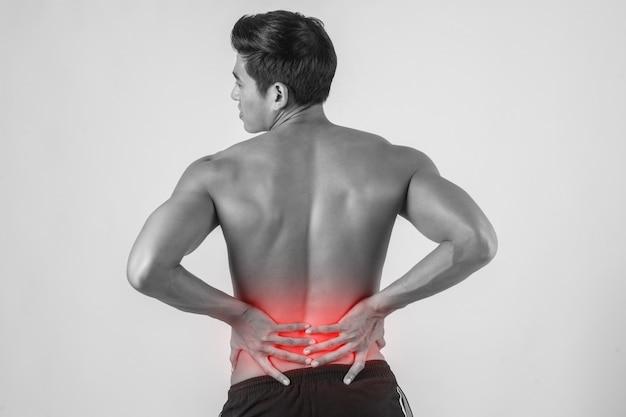 彼の痛みを伴う後ろをこすっている男の近くには、白い背景があります。 無料写真