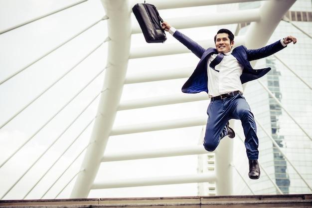 都市の通りを走っているブリーフケースを持つ若い実業家は、仕事に行くために急いでいます。 無料写真