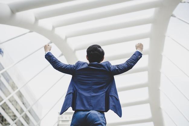 Успешно молодой бизнесмен держит оружие поднял и выражает позитивность, стоя на открытом воздухе Бесплатные Фотографии