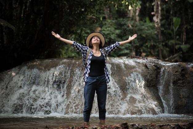 若い、女、楽しむこと、滝、森林 Premium写真