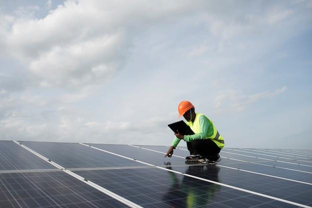 技術者のエンジニアは、太陽電池パネルのメンテナンスをチェックします。 無料写真