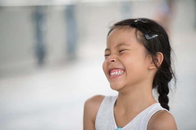 ストリートで笑う愛らしい小さな女の子 無料写真
