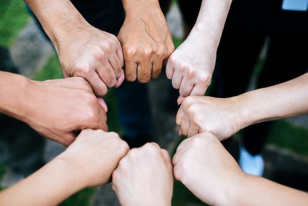 拳のバンプジェスチャーを作る手を立てて学生のクローズアップ。 無料写真