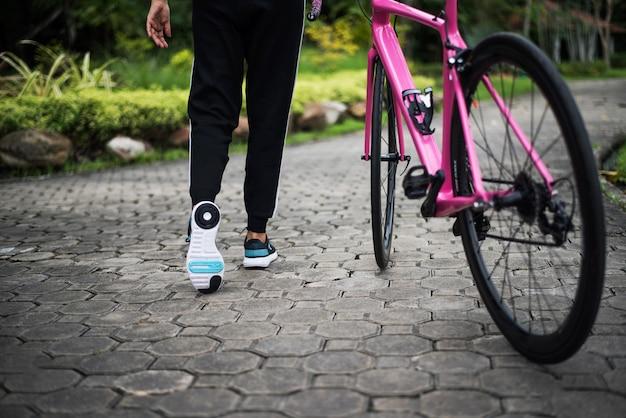 公園のロードバイクで女性の後部を閉じます。健康とスポーツのコンセプト。 無料写真