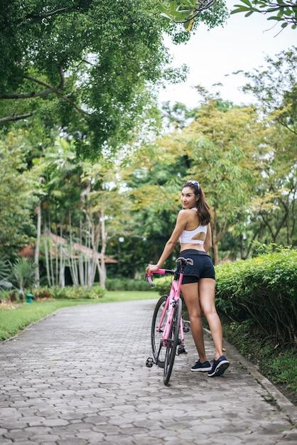 公園でピンクのバイクを持つ若い美しい女性の肖像画。魅力的な健康な女性。 無料写真