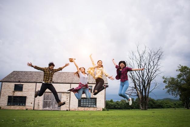 公園でジャンプする十代の学生の幸せなグループ 無料写真