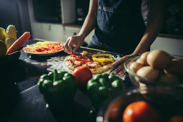 手作りのピザにトッピングを入れて女性の手を閉じます。 無料写真