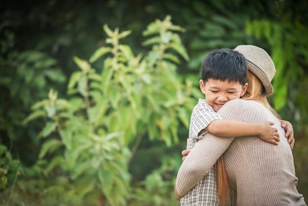 母と息子の肖像画は、一緒に公園で抱き合っています。家族のコンセプト。 無料写真