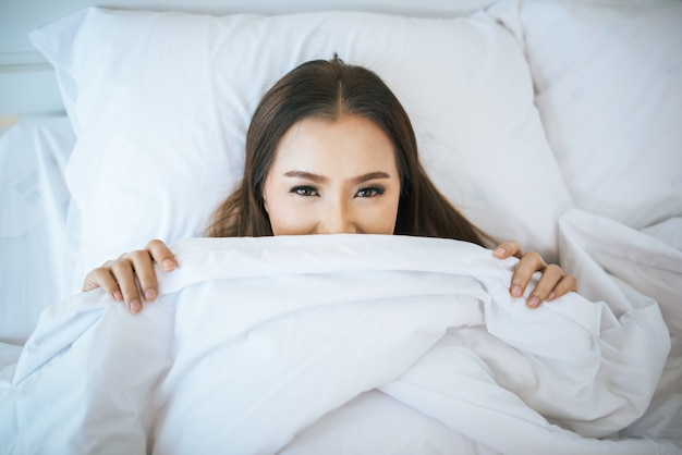 Красивая женщина просыпается в своей постели, ленив утром Бесплатные Фотографии