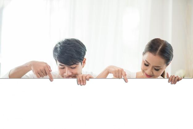 白い空白スペースを保持する幸せなカップルの手 無料写真