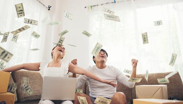 お金の雨の下でうまく座っている幸せなカップル。ビジネスオンラインコンセプト 無料写真
