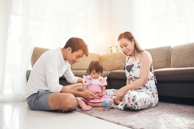 リビングルームの床で遊んでいる親と子供 無料写真