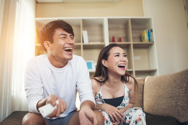 リビングルームでリラックスしてテレビを見ている幸せな若いカップル 無料写真