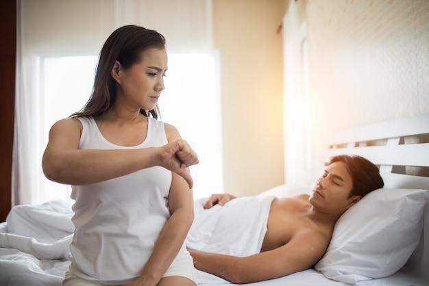 彼女のボーイフレンドとの関係の問題を考えて、悲しみのガールフレンドはベッドに座る 無料写真