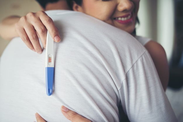 寝室で肯定的な妊娠検査を見つけた後に笑う幸せなカップル 無料写真