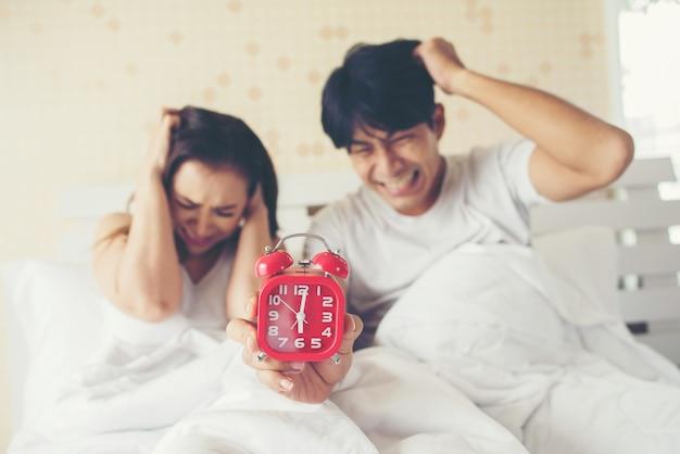 У пары возникают проблемы с вставанием рано утром на кровати Бесплатные Фотографии