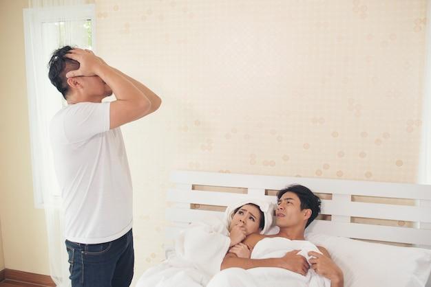夫は寝室に男と妻を見つけた。 無料写真