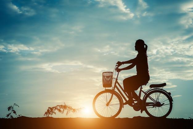 自転車と美しい空を持つ女性のシルエット 無料写真