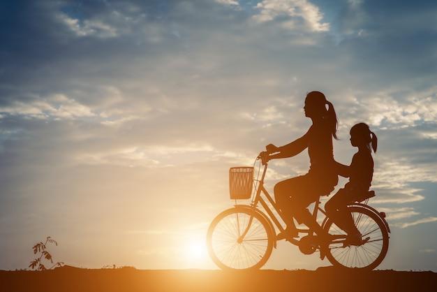 彼女の娘と自転車を持つ母のシルエット 無料写真