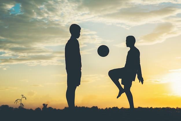 子供たちのシルエットがサッカーをする 無料写真