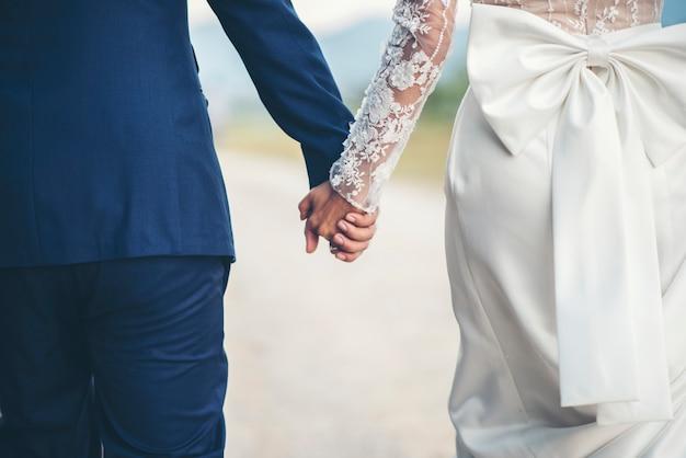 Крупным планом семейная пара, держась за руки в день свадьбы Бесплатные Фотографии
