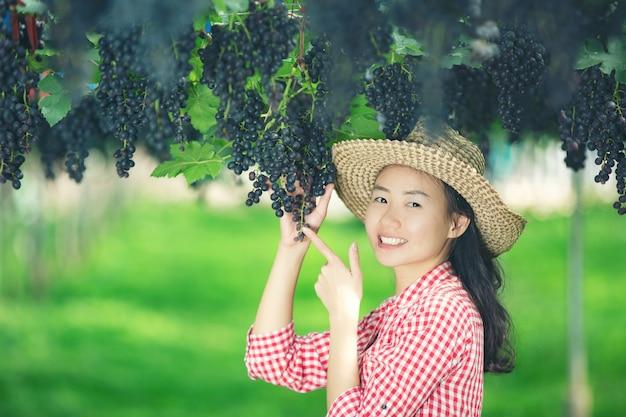 笑顔で収穫を楽しむブドウ畑の農家。 無料写真