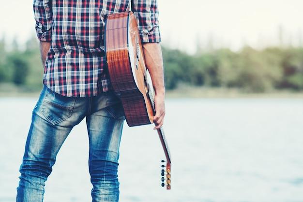 アコースティックギターを弾く大人のハンサムなミュージシャン 無料写真