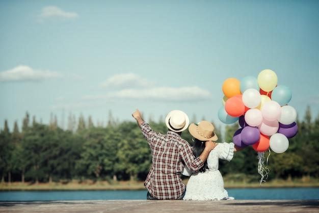 Портрет влюбленная пара с красочными воздушными шарами Бесплатные Фотографии