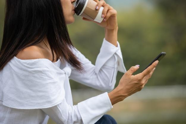 幸せな若い女がコーヒーを飲むと、スマートフォンを使用して 無料写真
