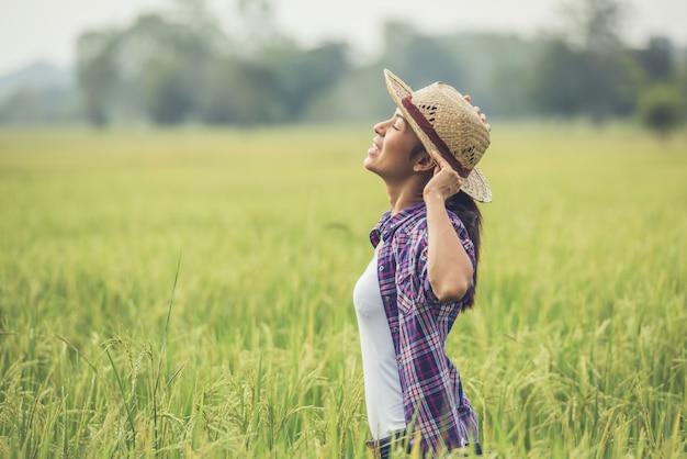 農夫は田んぼにいて、彼女の米の世話をします。 無料写真
