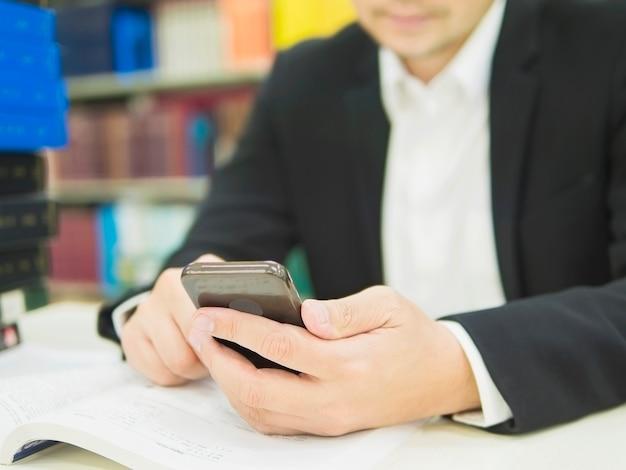ビジネスマンは彼のオフィスで働いている間携帯電話を使用しています。 無料写真