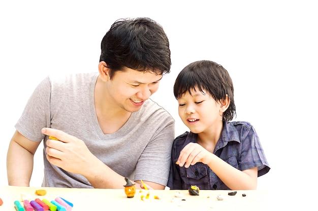 父は彼の息子とハロウィーンクレイを白い背景の上で遊んでいます。 無料写真