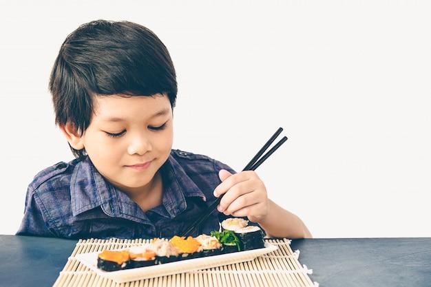 アジアの素敵な男の子のビンテージスタイルの写真は寿司を食べています。 無料写真