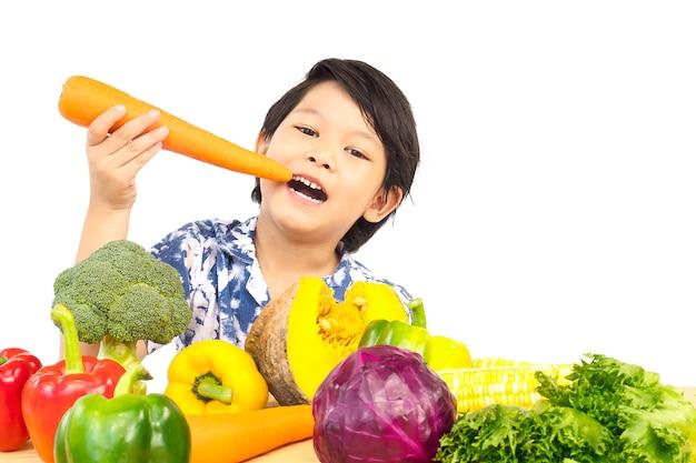 アジアの健康的な少年の様々な新鮮なカラフルな野菜と幸せな表情を示す 無料写真