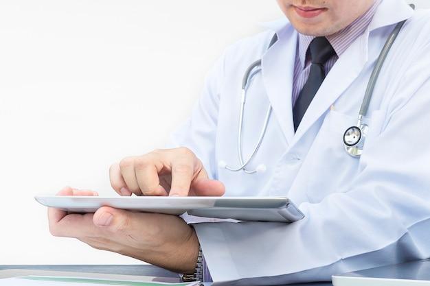 医者は白い背景の上のタブレットで働いています。 無料写真