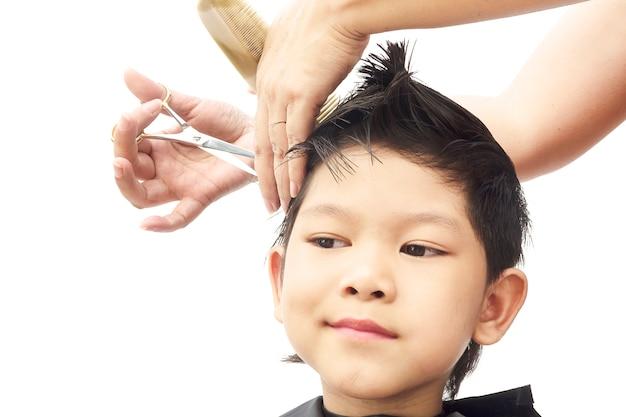 少年は白い背景で隔離された髪のドレッサーによって彼の髪をカットします。 無料写真