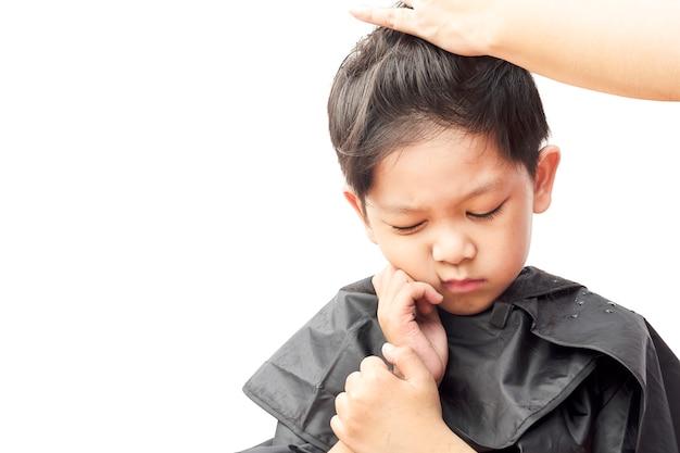 少年は白い背景で隔離されたヘアドレッサーで彼の髪をカットしながらかゆみを感じています。 無料写真