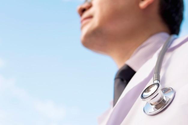 男性医師は青い空を見ています。医療サービスの未来のための概念 無料写真