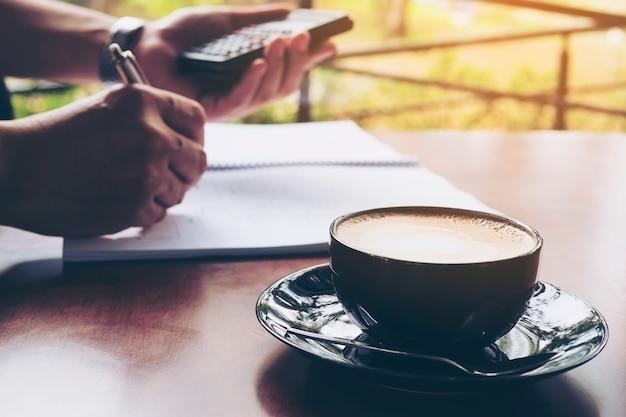 ビジネスマンはコーヒーショップで彼のコンピューターで働いています。 無料写真