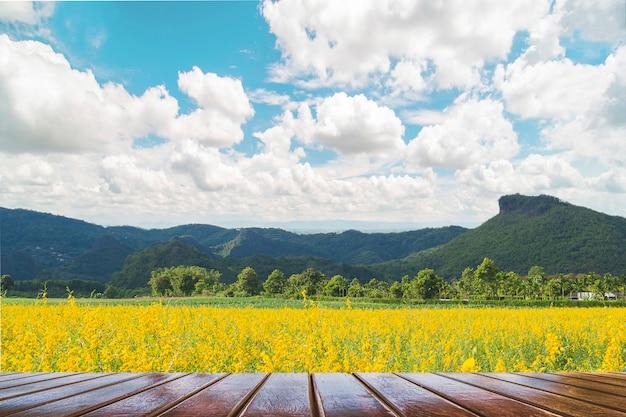美しい黄色の花畑と山の青い空の風景の上の木のテラス 無料写真