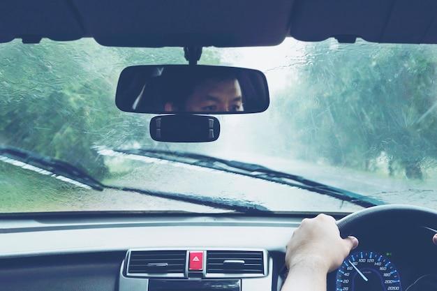 Человек за рулем автомобиля в сильный дождь Бесплатные Фотографии