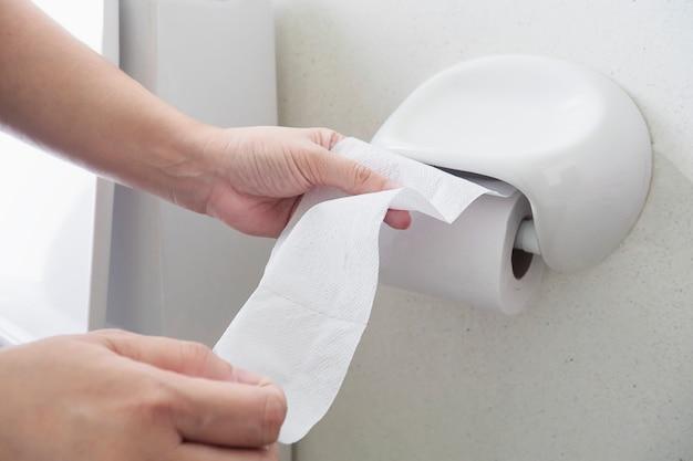 トイレでティッシュを引っ張っている女性 無料写真