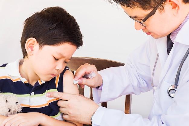 白い背景の上の男性医師によって扱われている病気のアジアの少年 無料写真