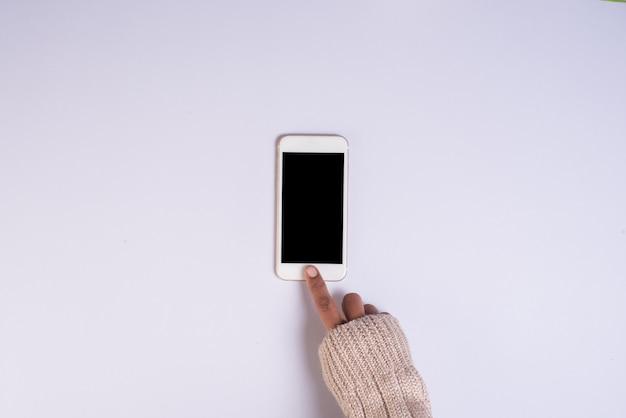 白い背景の上の携帯電話を持つトップビュー手 無料写真