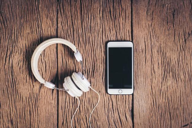 トップビュー電話とヘッドフォンの木製の背景 無料写真