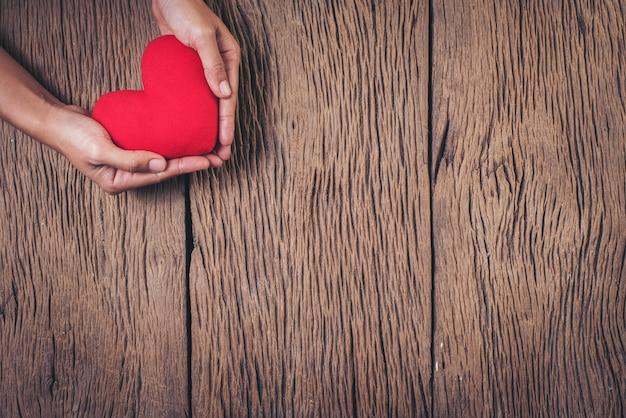 木材の背景に赤いハートを持っている手 無料写真