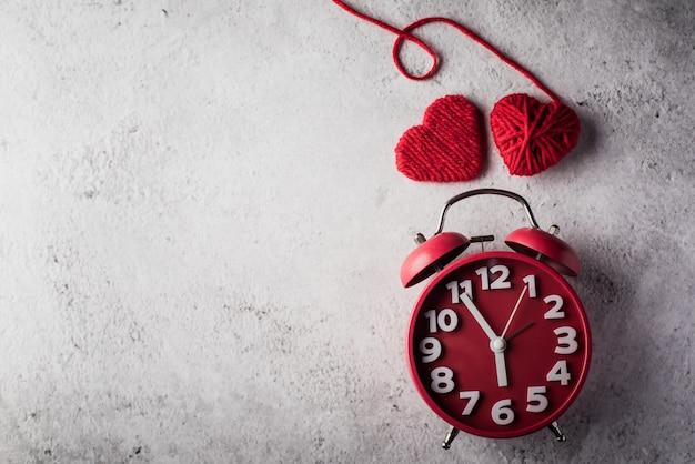 赤いハート、バレンタインの日の概念と赤い目覚まし時計。 無料写真