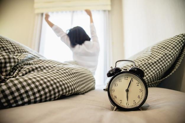 女性は新鮮な朝のために怠惰にストレッチ自分を目覚めさせる 無料写真