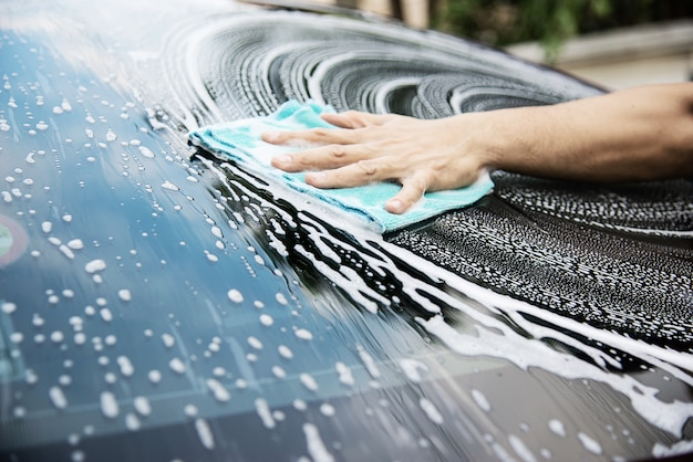 Человек моет машину с помощью шампуня Бесплатные Фотографии